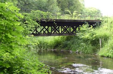 Jernbanebroen genbrugt over Sæby å - nu som underbygning til Humlebroen i Sæbygård Skov.