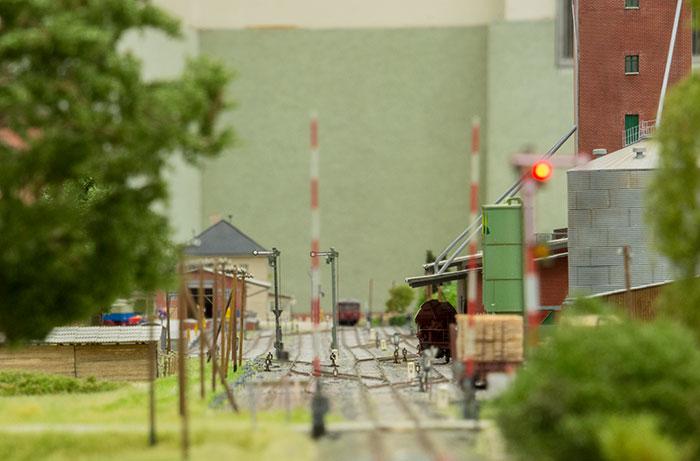 Stationsareal med jernbaneoverskæring i forgrunden