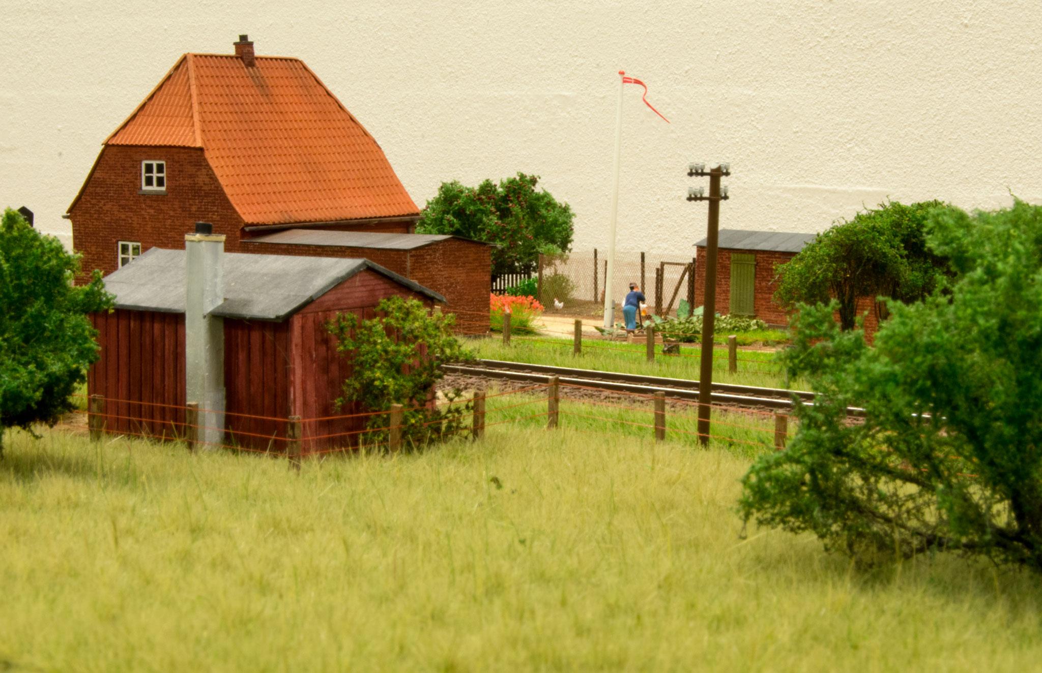 Ledvogterhuset i Søbylund med blomsterbede, flagstang og hønsehus