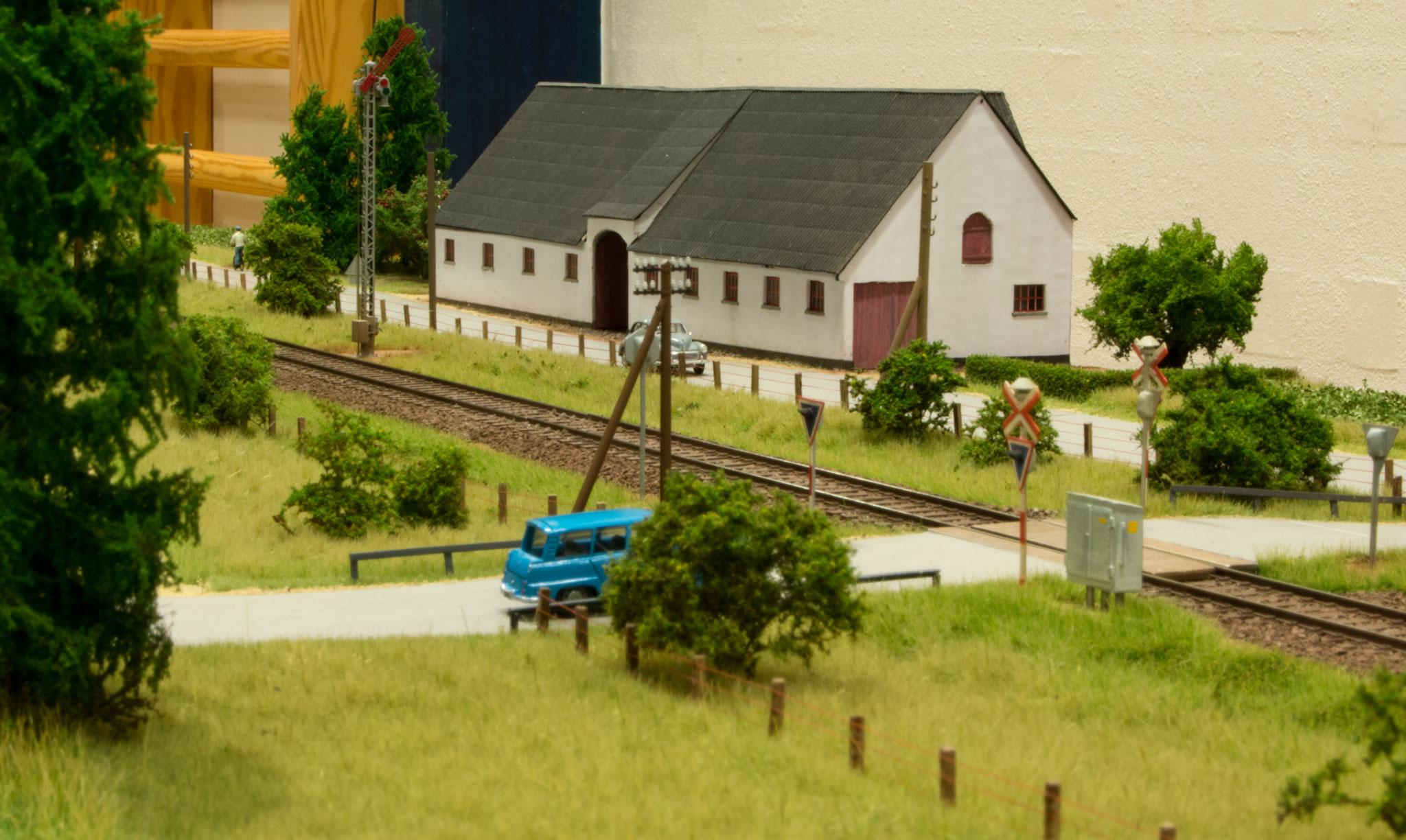 Den hvide gård ved Søbylund med port ind til gården, armsignal ved sporet og jernbaneoverskæringen i forgrunden