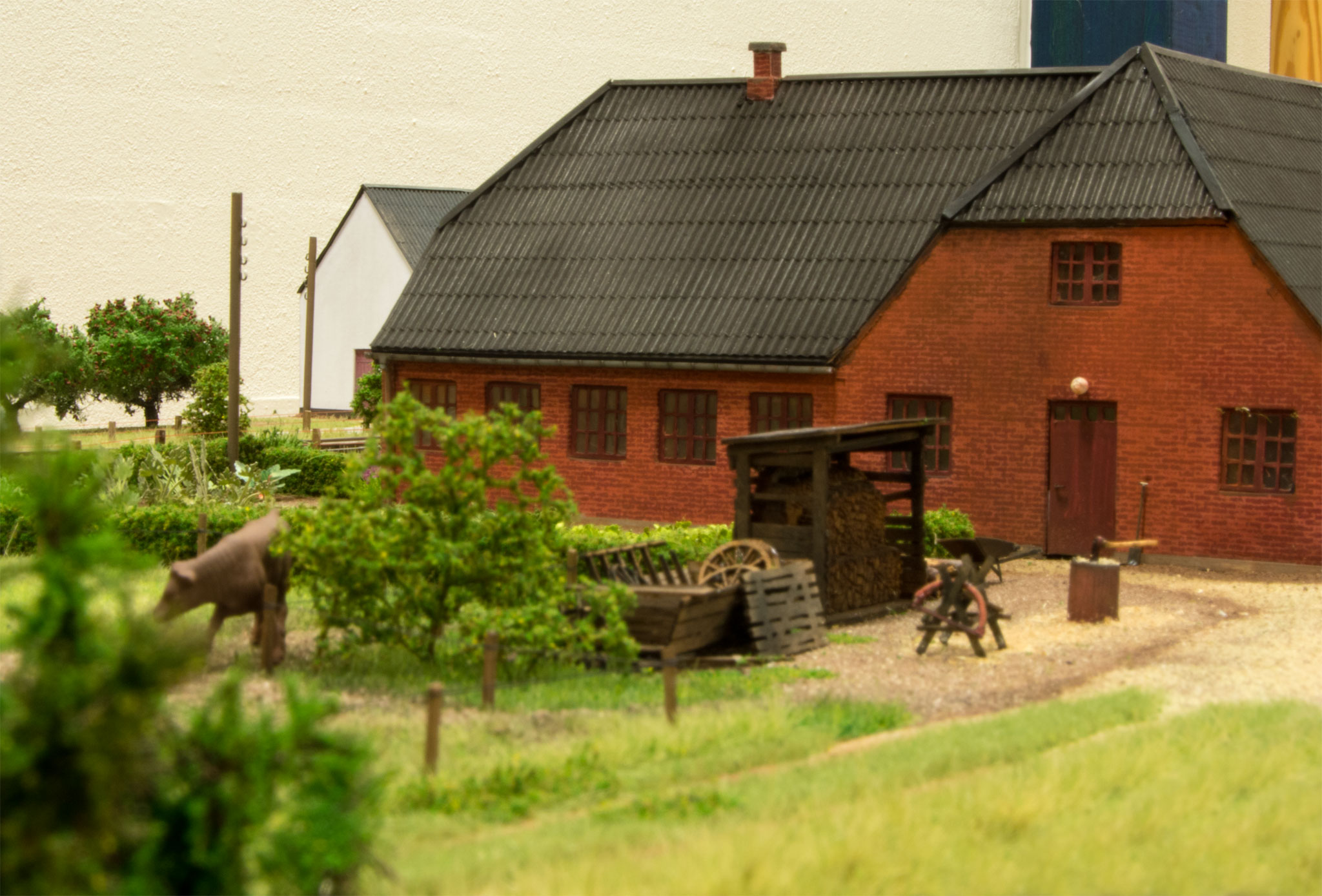 Skråt overfor den hvide gård ligger denne rødstensgård, hvor stemningen understreges af brændestabel, bukke, sav og økse i træstub